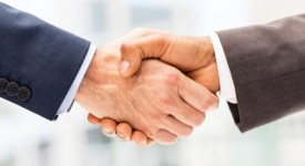 Close-up of professional partners shaking hands after business deal. Horizontal shot.